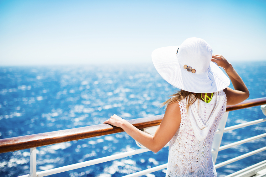 Unrecognizable woman with hat on a cruise ship looking at the view.